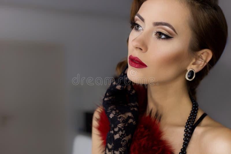 La mujer joven atractiva hermosa hace alarde del frente del espejo en el vestuario en ropa interior de encaje en un estilo retro  imagen de archivo libre de regalías