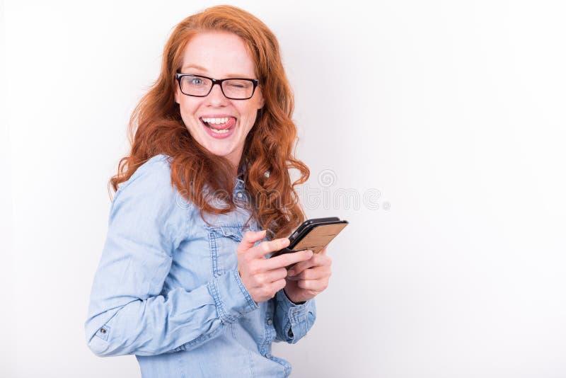 La mujer joven atractiva le gusta lo que ella ve en el smartphone fotos de archivo