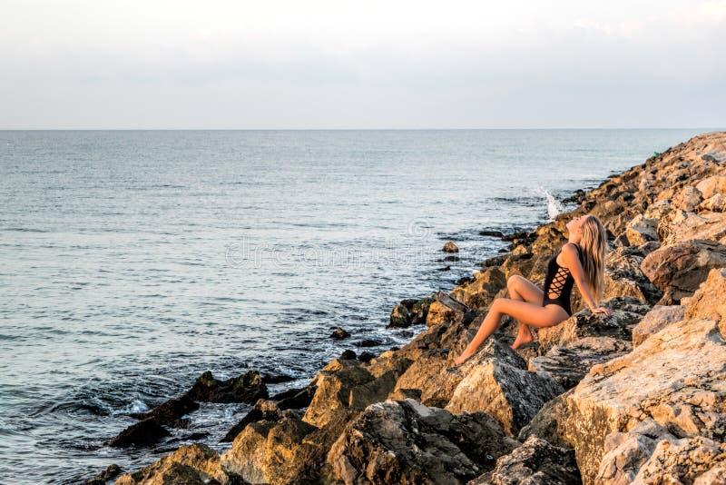 La mujer joven atractiva resuelve la salida del sol en las rocas cerca del mar fotografía de archivo libre de regalías