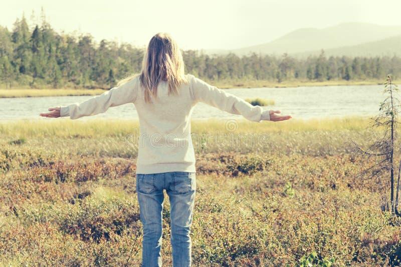 La mujer joven aumentó las manos que colocaban viaje al aire libre solamente que caminaba foto de archivo libre de regalías