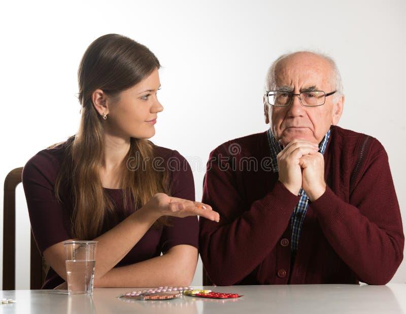 La mujer joven ayuda al hombre mayor fotografía de archivo libre de regalías