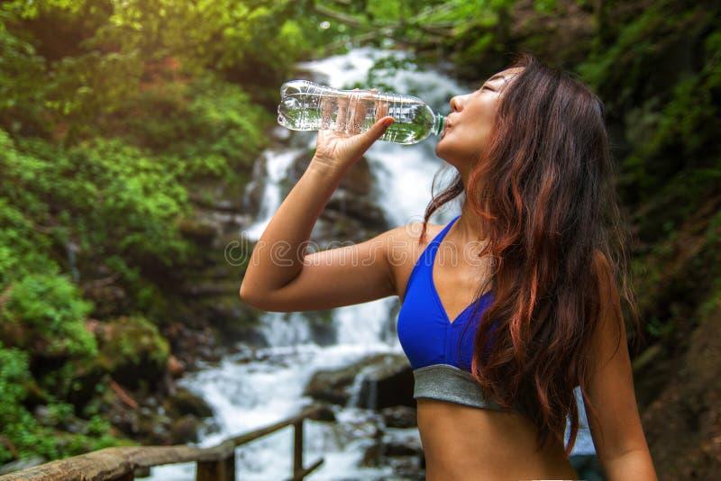 La mujer joven bebe el agua en un fondo de la cascada fotografía de archivo