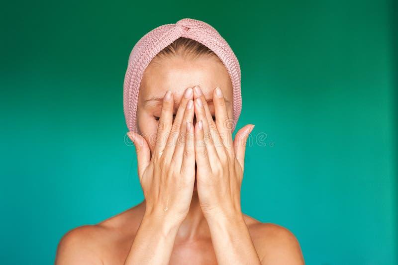 La mujer joven blanca pone una mascarilla en casa en un fondo de la turquesa Mujer europea que se lava la cara con cierre del agu imagen de archivo libre de regalías