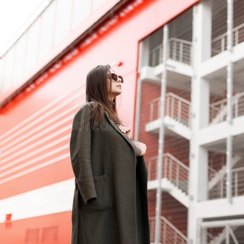 La mujer joven bonita con las gafas de sol en una capa del verde del vintage de la moda se coloca en la ciudad contra la perspect imagen de archivo libre de regalías