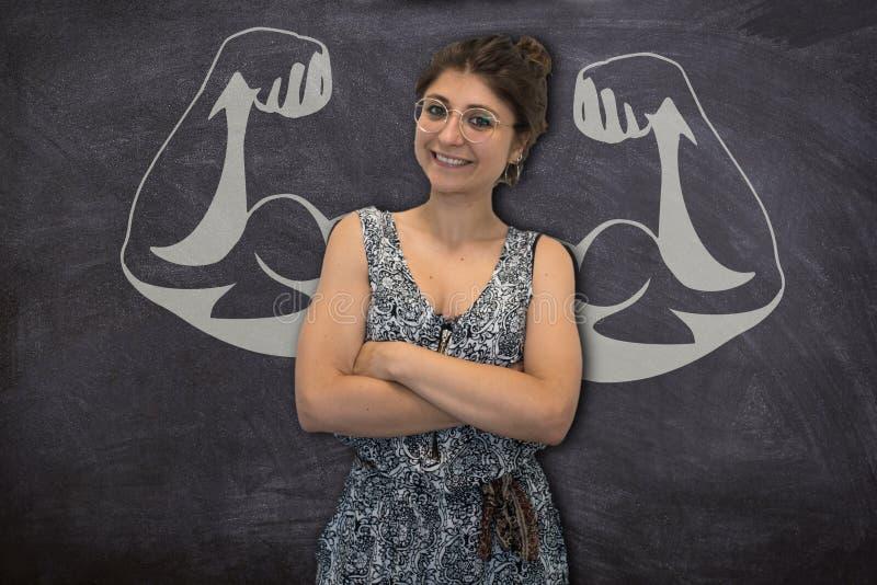 La mujer joven bonita con los músculos dibujados en una pizarra expresa el concepto de determinación y de fuerza femeninas imagen de archivo libre de regalías