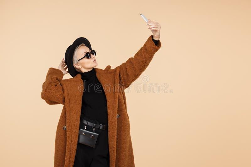 La mujer joven bonita del inconformista con el pelo corto rubio que lleva una capa, el sombrero y las gafas de sol hacen el selfi fotos de archivo libres de regalías