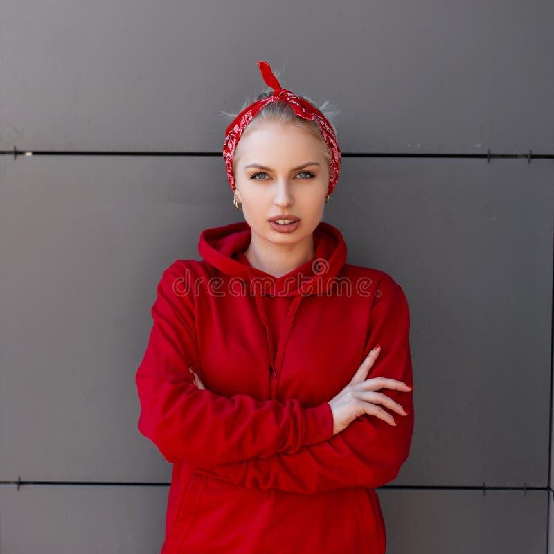 La mujer joven bonita elegante en ropa de moda moderna con un pañuelo rojo se está colocando cerca de un edificio moderno gris imagen de archivo libre de regalías