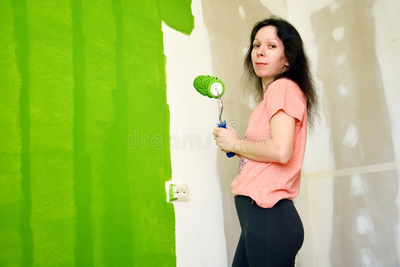 La mujer joven bonita en camiseta rosada es sonriente y que mantiene el rodillo, pintando la pared interior verde un nuevo hogar fotos de archivo libres de regalías