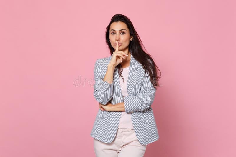 La mujer joven bonita en chaqueta rayada que dice silencio sea reservada con el finger en gesto de los labios shhh aislado en pas fotografía de archivo