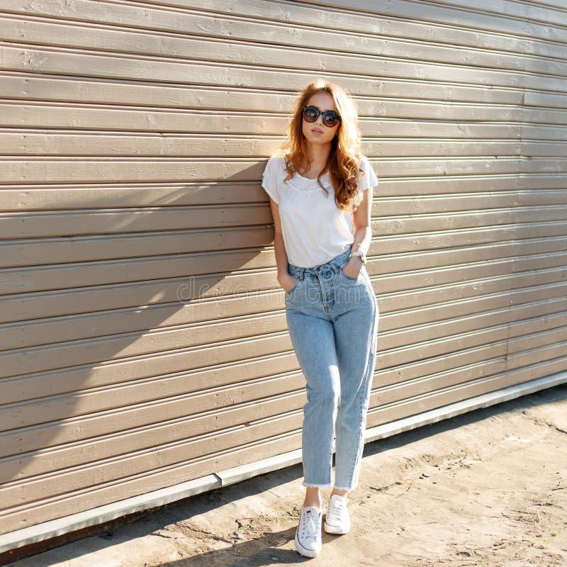 La mujer joven bonita europea del inconformista en camiseta blanca elegante en vaqueros del vintage en gafas de sol de moda se es imagen de archivo