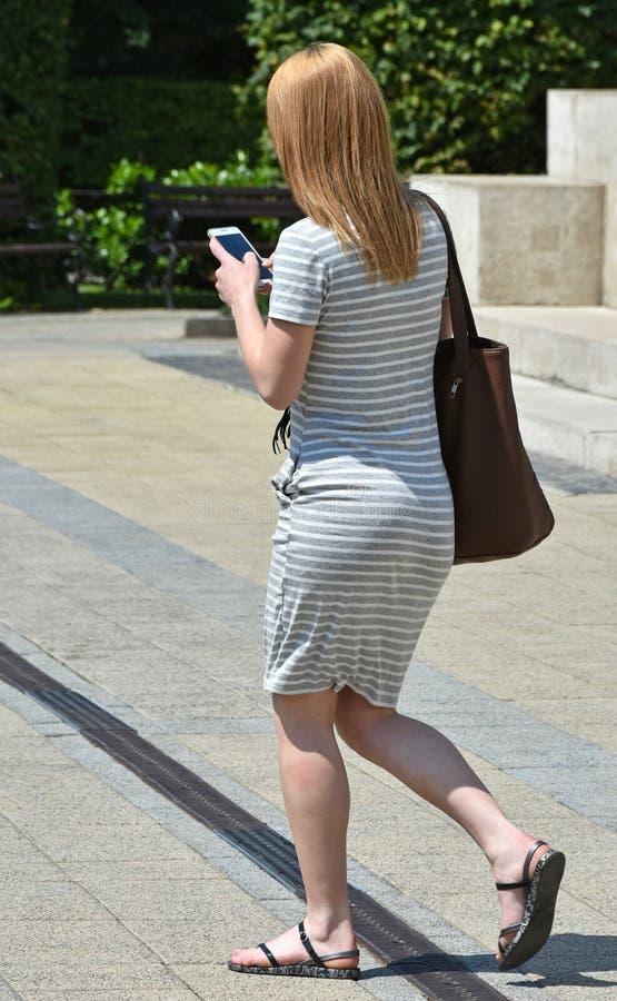 La mujer joven camina con un smartphone fotos de archivo