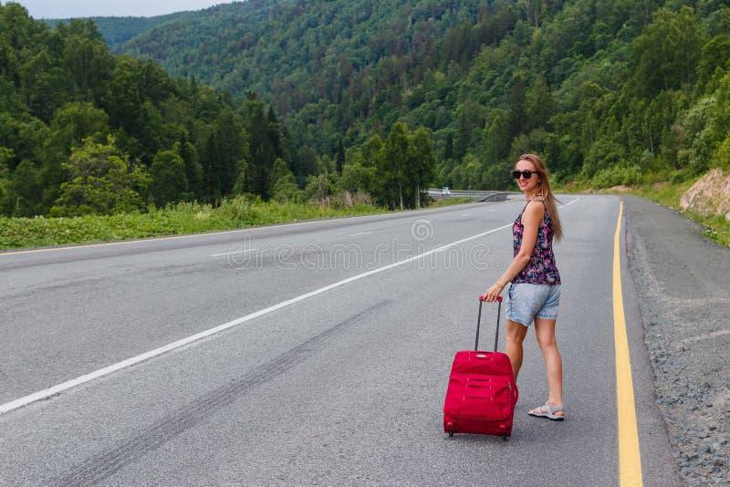 La mujer joven camina a lo largo del camino con una maleta imagen de archivo