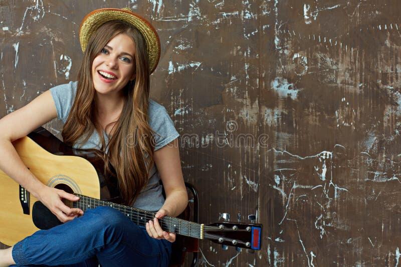 La mujer joven canta y juega en gitar imagenes de archivo