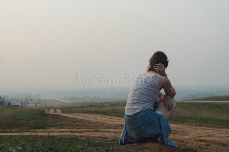 La mujer joven caucásica blanca que se sienta en la colina cerca del camino, guarda el cuello de la mano fotografía de archivo