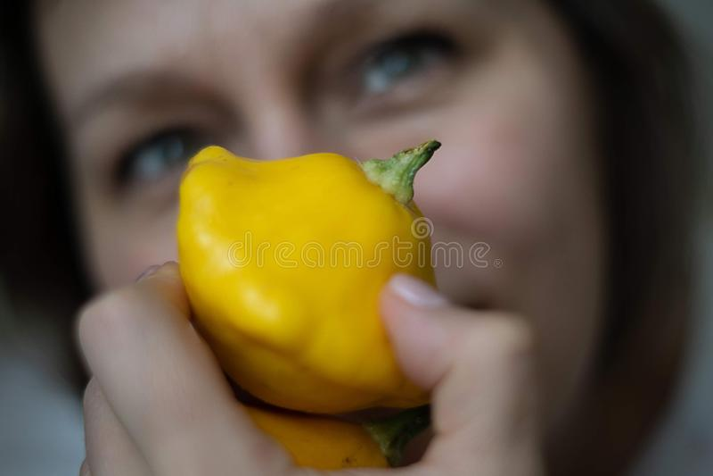 La mujer joven celebra la pequeña calabaza amarilla y sonrisas foto de archivo libre de regalías
