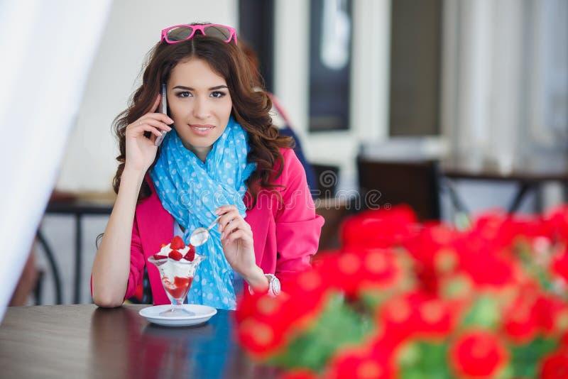 La mujer joven come el postre y hablar en el teléfono fotografía de archivo