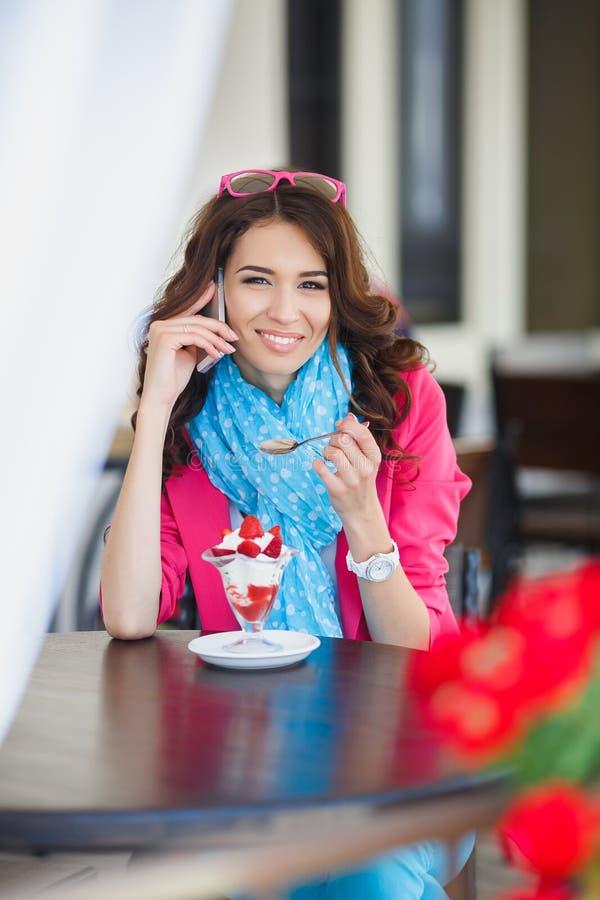 La mujer joven come el postre y hablar en el teléfono fotos de archivo