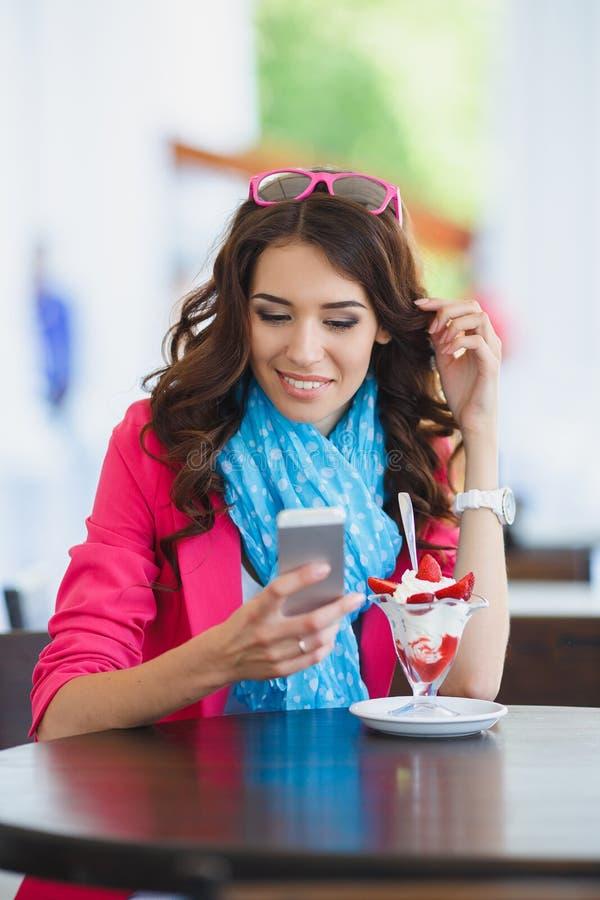 La mujer joven come el postre y hablar en el teléfono imagen de archivo