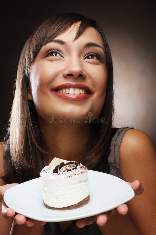 La mujer joven come una torta dulce imagen de archivo