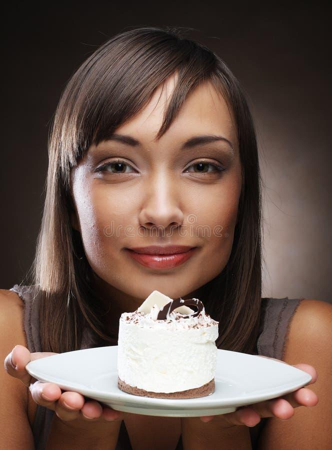 La mujer joven come una torta dulce fotos de archivo