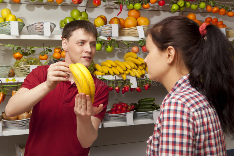 La mujer joven compra el plátano imagen de archivo