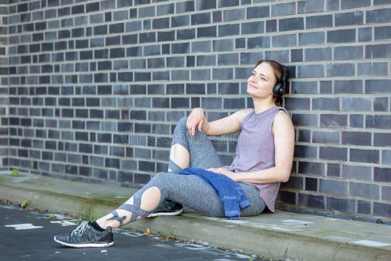 La mujer joven con el auricular toma la rotura después de su entrenamiento foto de archivo