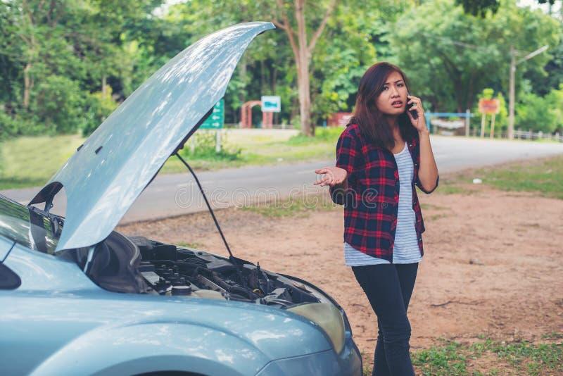 La mujer joven con el coche analiza y ella está llamando el emergenc fotos de archivo