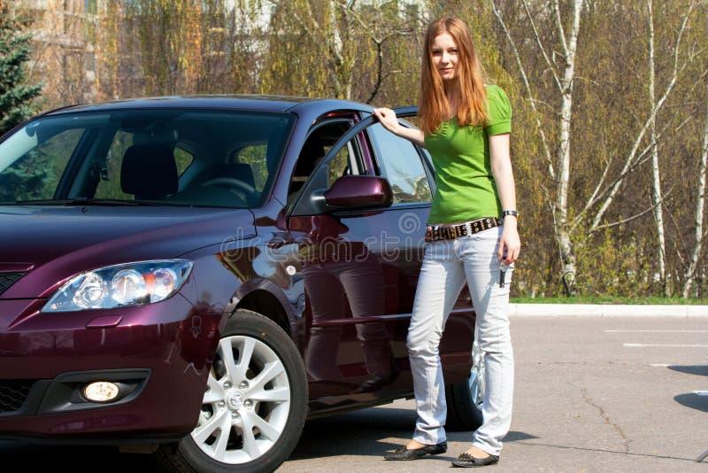 La mujer joven con el nuevo coche imagen de archivo libre de regalías