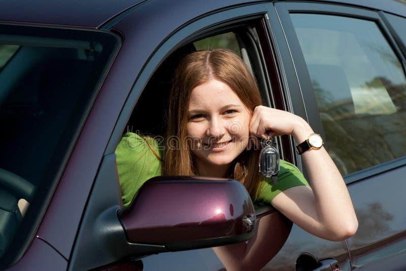 La mujer joven con el nuevo coche fotografía de archivo libre de regalías