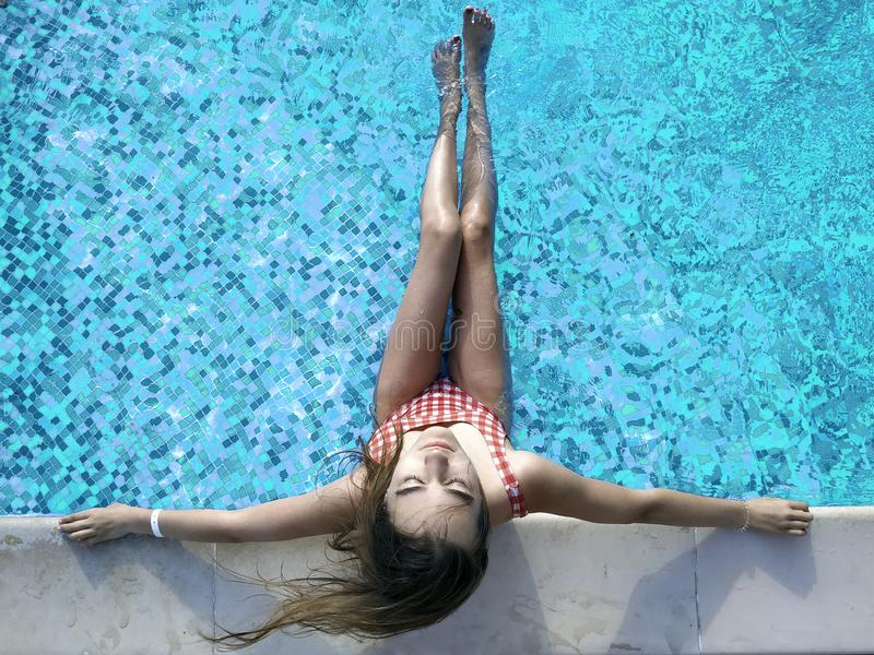 La mujer joven con el pelo largo, con los ojos cerrados se está relajando en la piscina en el balneario imagen de archivo