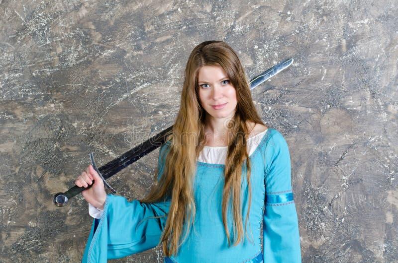 La mujer joven con el pelo largo presenta con la espada foto de archivo
