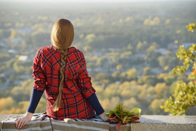 La mujer joven con el pelo largo se sienta en una colina que pasa por alto la ciudad fotos de archivo libres de regalías