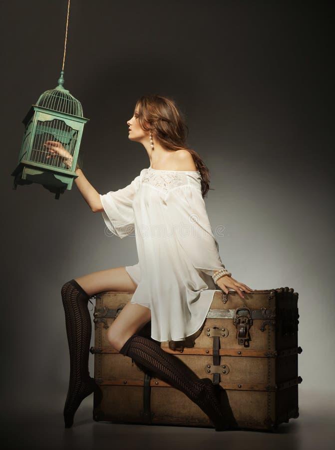 La mujer joven con el pelo largo y el blanco visten sentarse en suitca grande foto de archivo libre de regalías