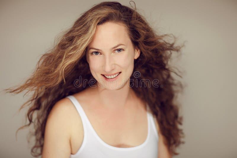 La mujer joven con el pelo rizado largo y naturales hermosos componen el retrato de la belleza imagen de archivo