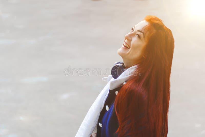 La mujer joven con el pelo rojo con los auriculares en una capa azul r?e la mirada para arriba en fondo gris Copyspace foto de archivo libre de regalías