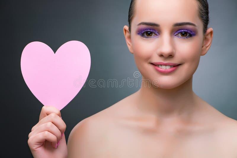 La mujer joven con la forma del corazón para su mensaje fotos de archivo libres de regalías