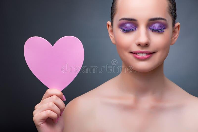 La mujer joven con la forma del corazón para su mensaje fotografía de archivo