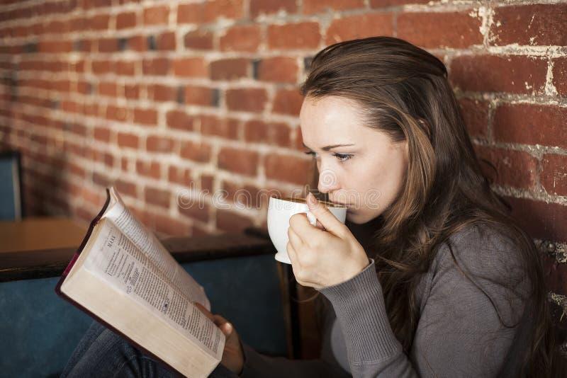 La mujer joven con la taza del café con leche lee su biblia fotos de archivo