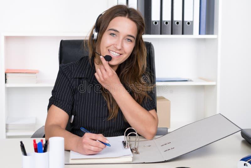 La mujer joven con las auriculares está escribiendo en un fichero imagen de archivo libre de regalías