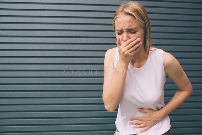La mujer joven con las manos en el estómago que tiene malos dolores duele en fondo gris Intoxicación alimentaria, gripe, calambre fotos de archivo libres de regalías