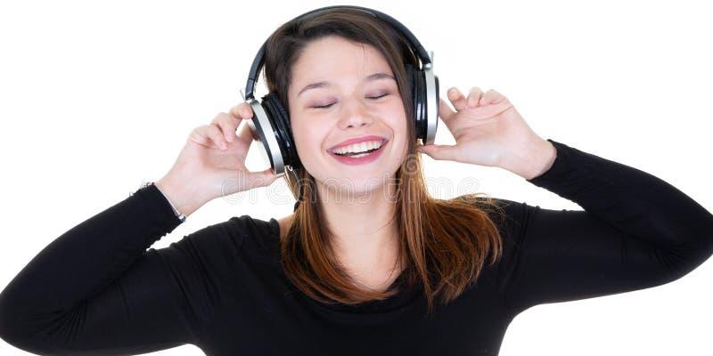 La mujer joven con los auriculares escucha la música y se siente bien ojos cerrados fotos de archivo