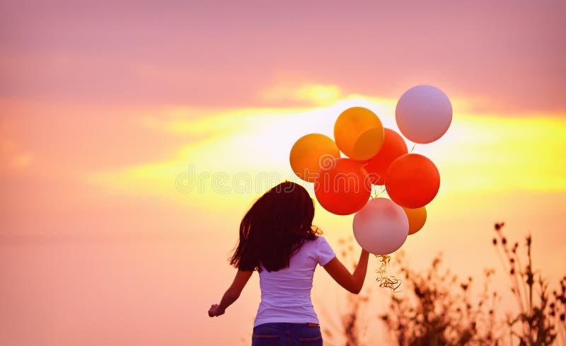 La mujer joven con los balones de aire que funcionan con verano coloca, en puesta del sol imagen de archivo