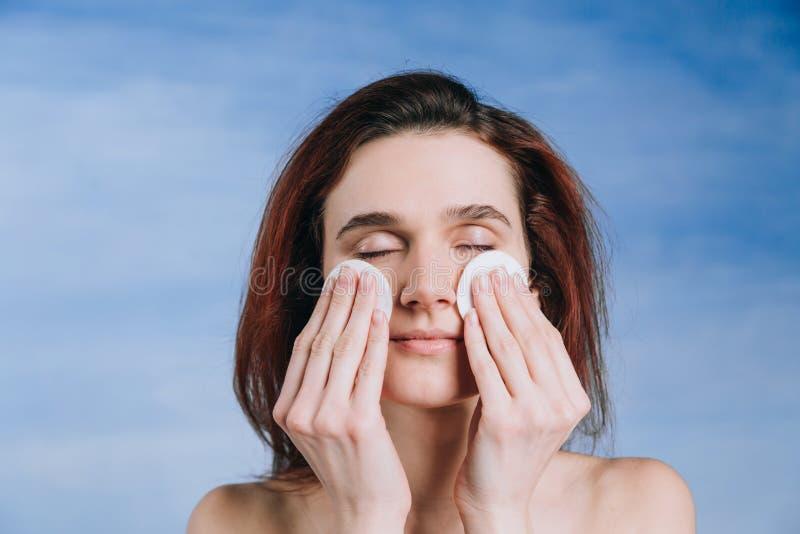 La mujer joven con los cojines de dos esponjas del wihte de un algodón del fondo limpia la piel del problema con los ojos cerrado foto de archivo