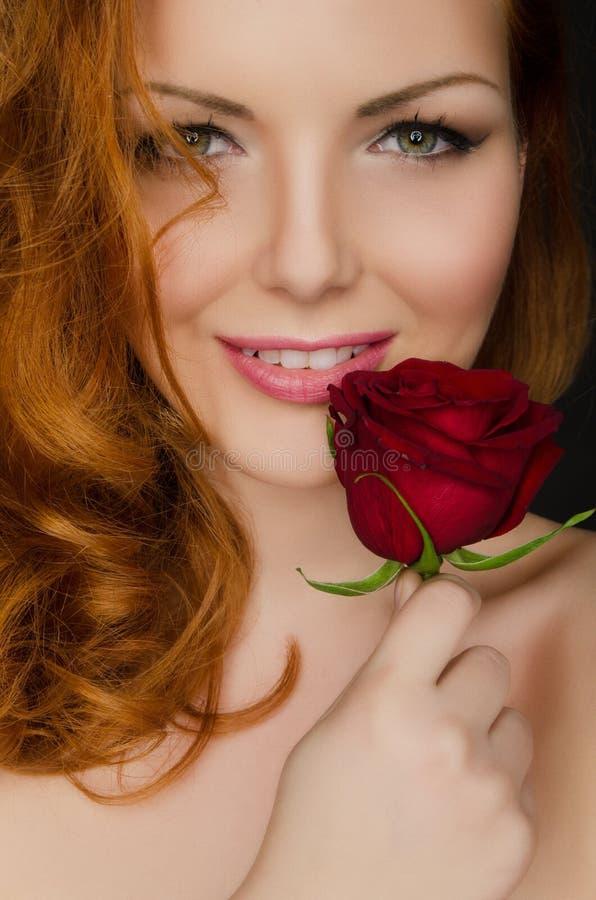La mujer joven con los controles rojos del pelo subió en sus manos fotografía de archivo