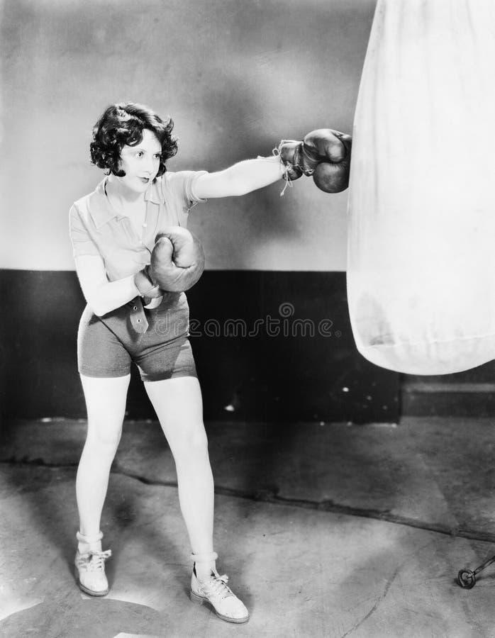 La mujer joven con los guantes de boxeo entrena con un saco de arena (todas las personas representadas no son vivas más largo y n imágenes de archivo libres de regalías