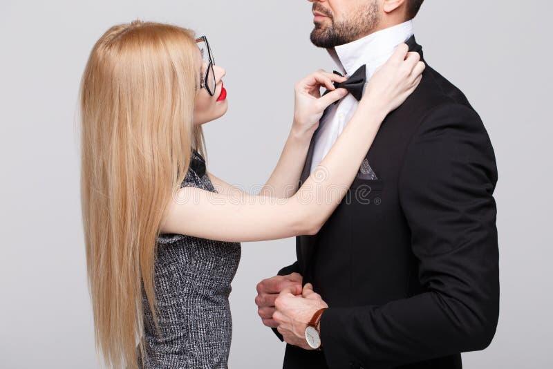 La mujer joven con los labios rojos endereza la corbata de lazo del hombre foto de archivo