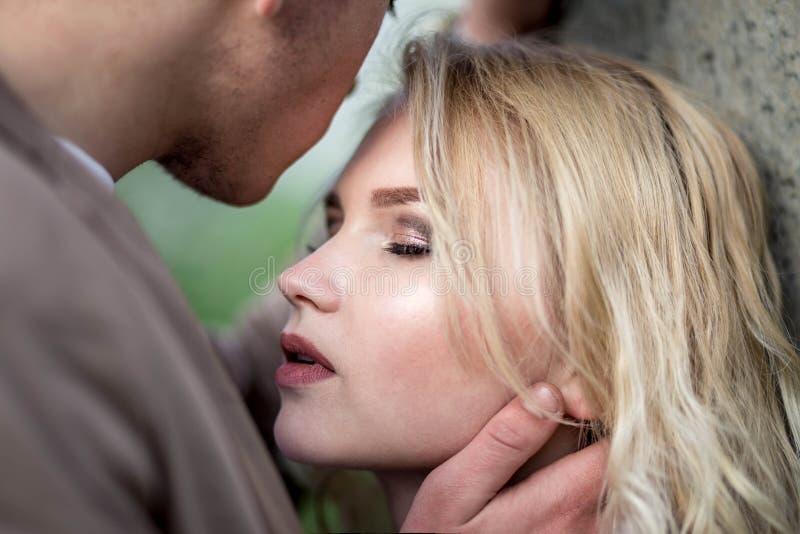 La mujer joven con los ojos cerrados mientras que hombre foto de archivo libre de regalías