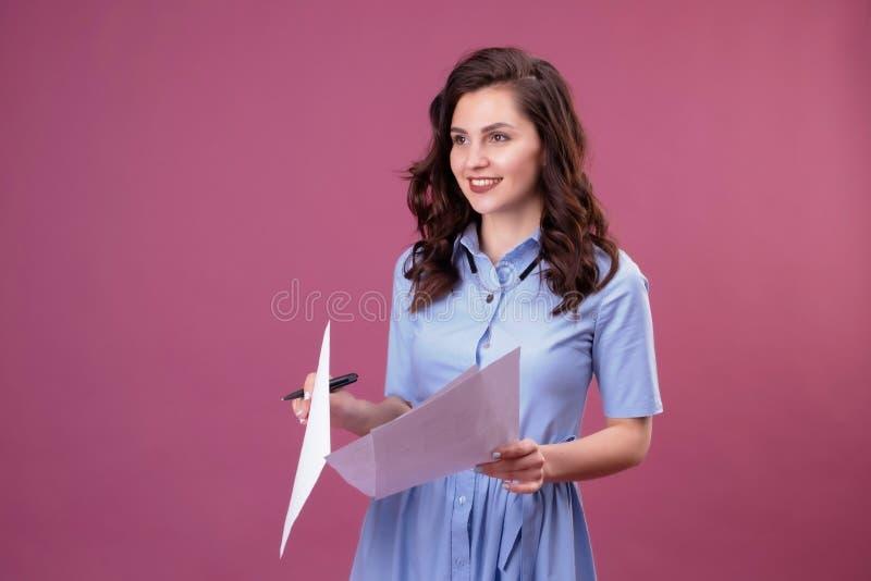 La mujer joven con los puntos a las hojas de papel, sostiene una pluma imagenes de archivo