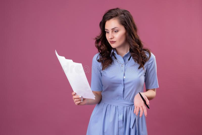 La mujer joven con los puntos a las hojas de papel, sostiene una pluma fotos de archivo