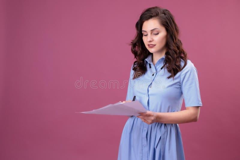 La mujer joven con los puntos a las hojas de papel, sostiene una pluma imagen de archivo